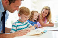 Parents helping children with homework in kitchen looking over shoulder at textbook Royalty Free Stock Photos