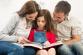 Parents helping daughter in studies mother and father their while reading book Stock Image