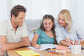 Parents helping her daughter doing her homework at desk in living room Royalty Free Stock Photos