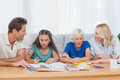 Parents helping their children doing their homework in living room Royalty Free Stock Images