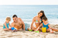 Parents helping toddlers to dig sand positive at beach Royalty Free Stock Photos