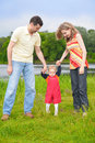 Parents hold for hands of child going on grass Royalty Free Stock Photos