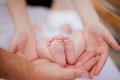 Parents holding the foot of their newborn with rings Stock Photo