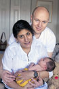 Parents holding their newborn baby at home Stock Photo