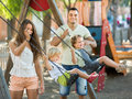 Parents with kids at swings smiling young family of four playground s focus on woman Royalty Free Stock Photo