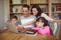 Parents and kids using laptop on table in study room Royalty Free Stock Photo