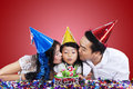 Parents kiss their child in birthday party Royalty Free Stock Photo