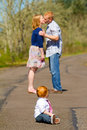 Parents kissing with baby in this selective focus image the of a one year old boy are out of focus in the background Stock Photography