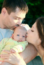 Parents kissing beautiful baby girl Royalty Free Stock Photo
