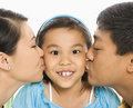 Parents kissing girl. Royalty Free Stock Image
