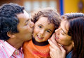 Parents kissing son portrait Royalty Free Stock Photo