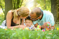 Parents are kissing their son happy interracial family is enjoying a day in the park Royalty Free Stock Images