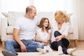 Parents and little girl sitting on floor at home family child concept smiling Stock Image