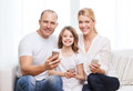 Parents and little girl with smartphones at home family child technology concept smiling Royalty Free Stock Images