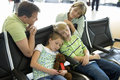 Parents looking at children sleeping on seats in airport departure lounge, girl (7-9) holding soft toy Royalty Free Stock Photo