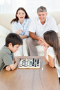 Parents looking their children playing chess Stock Photo