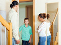 Parents meeting with scold of teenage son in doorway at home Royalty Free Stock Photo