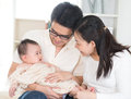 Parents pampering baby asian six months old girl at home Stock Photo