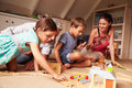 Parents playing with kids and toys in an attic playroom Royalty Free Stock Photo