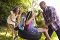 Parents Pushing Children On Tire Swing In Garden Royalty Free Stock Photo