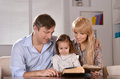 Parents reading a book their daughter happy at home Royalty Free Stock Photos