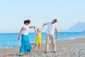 Parents shake their little son on the beach Royalty Free Stock Photo