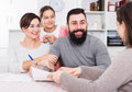 Parents signing property papers Royalty Free Stock Photo