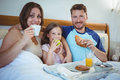 Parents sitting on bed with daughter and having breakfast Royalty Free Stock Photo