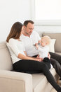 Parents sitting on the sofa and looking at their beautiful baby girl playing with cell phone. Royalty Free Stock Photo