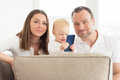 Parents sitting on the sofa. Their beautiful baby girl playing with cell phone. Royalty Free Stock Photo