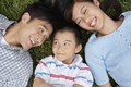 Parents with son lying on grass closeup of cheerful Royalty Free Stock Photography