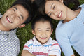 Parents with son lying on grass closeup portrait of smiling Royalty Free Stock Photo