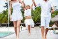 Parents swinging daughter as they walk along wooden jetty towards camera Royalty Free Stock Photo
