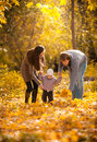 Parents teaching small daughter to walk at park young autumn Stock Photography