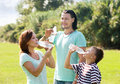 Parents with teenager son drinking cold water happy from plastic bottles in summer park Stock Image