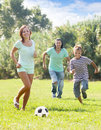Parents with teenager son playing with soccer ball happy at summer park Stock Photo