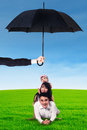 Parents and their child lying on grass under umbrella Royalty Free Stock Photo