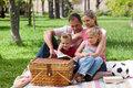 Parents and their children reading in the park Stock Image