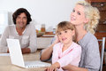 Parents and their daughter her smiling in the kitchen a computer is on the table Royalty Free Stock Images