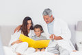 Parents with their son on bed looking together at photograph alb album home Royalty Free Stock Photography
