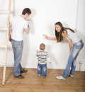 Parents with their son near ladder portrait of happy family doing repair Stock Images