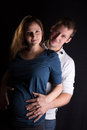 Parents to be attractive young hold their hands over their unborn child low key studio portrait Stock Image