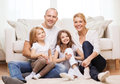 Parents and two girls sitting on floor at home family children concept smiling family with little Royalty Free Stock Photos