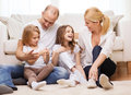 Parents and two girls sitting on floor at home family children concept smiling family with little Royalty Free Stock Image