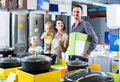 Parents with two kids choosing kitchenware in home appliance sto Royalty Free Stock Photo