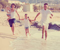 Parents with two kids jogging on beach