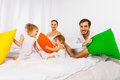 Parents and two kids playing with colorful pillows Royalty Free Stock Photo