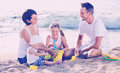 Parents with two kids playing with toys on beach
