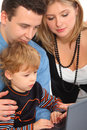 Parents whit son look on notebook close up Royalty Free Stock Photos