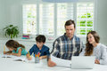 Parents working with laptop and childrens studying in living room Royalty Free Stock Photo